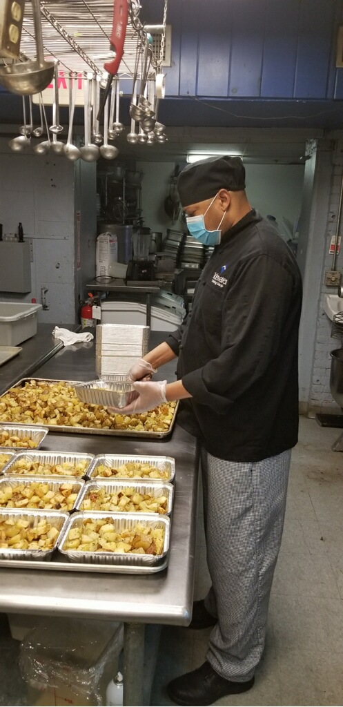 A Tidewater Catering chef prepares take-home dinners for four, donated by Bellwether Community Credit Union for local hospitals.