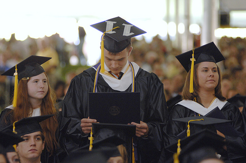 graduating students wiht diplomas