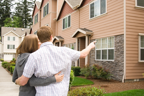 couple pointing at house