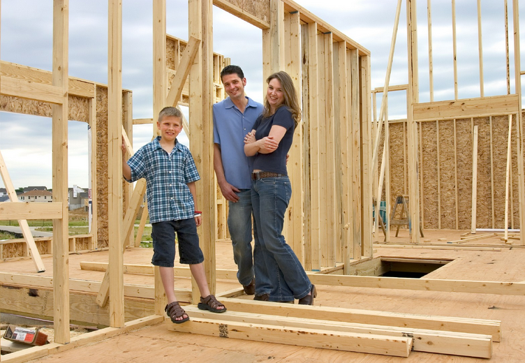 couple and son standing in partially constructed house