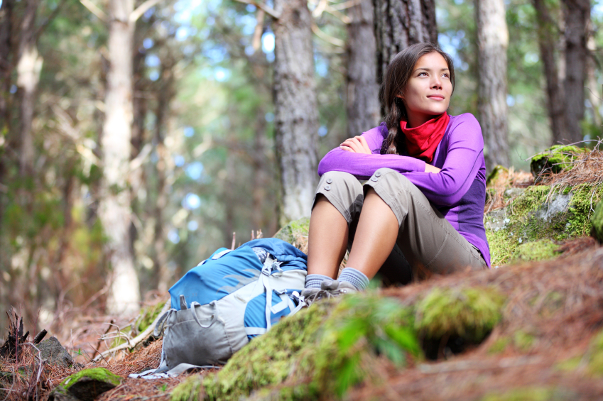 woman with rucksack sitting in woods